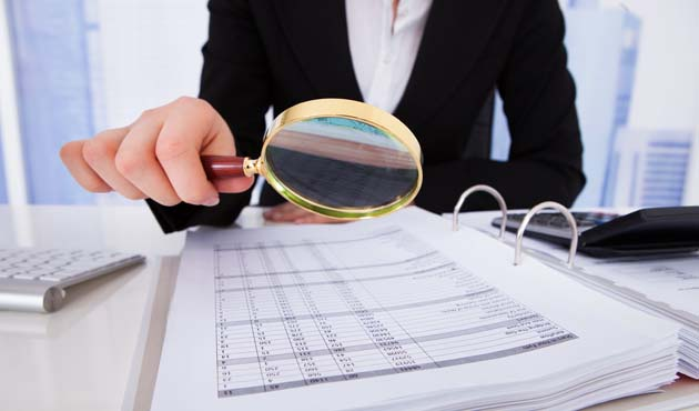 Businesswoman Scrutinizing Bills With Magnifying Glass