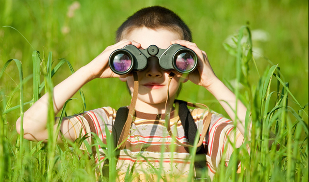 5126252 - young boy in a field looking through binoculars