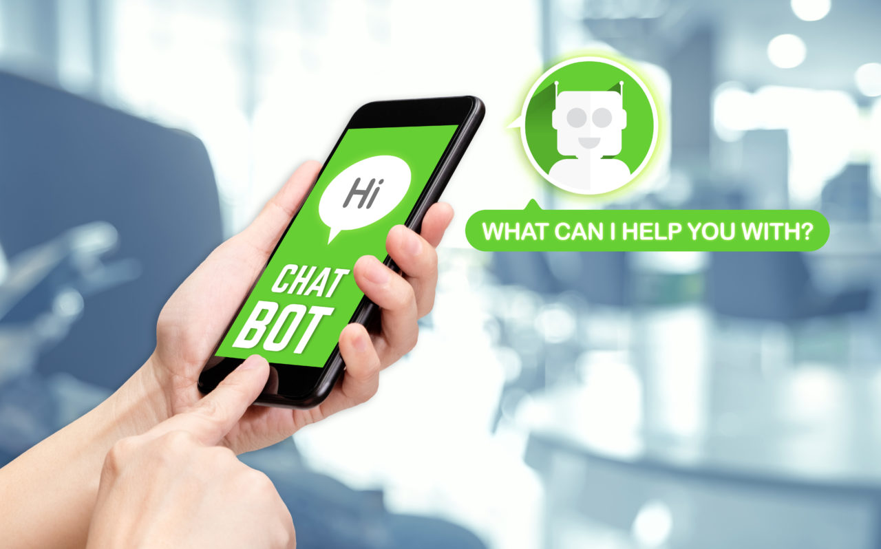 Hand holding mobile chat with bot on mobile message app with blu