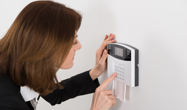 Woman Entering Code In Security System