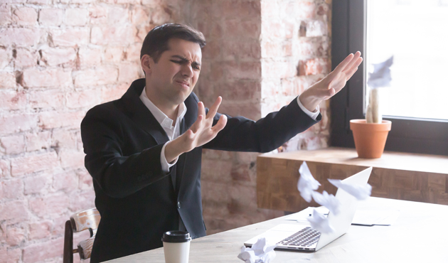 Stressed tired and annoyed employee throwing crumpled paper
