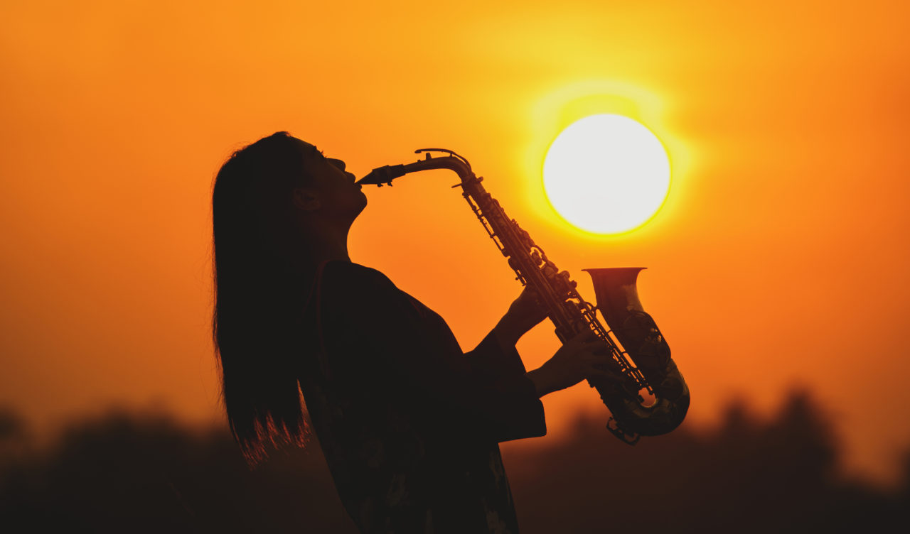 silhouette young woman playing the saxophone