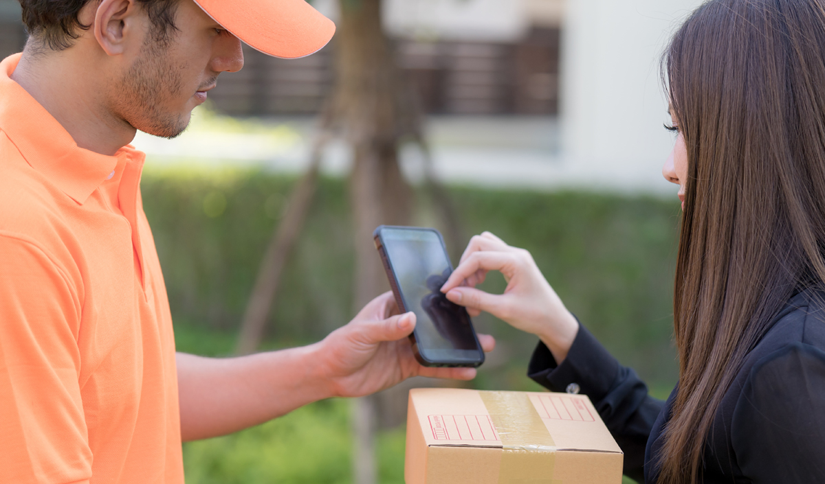 Business woman is signing on mobile device receiving package delivery