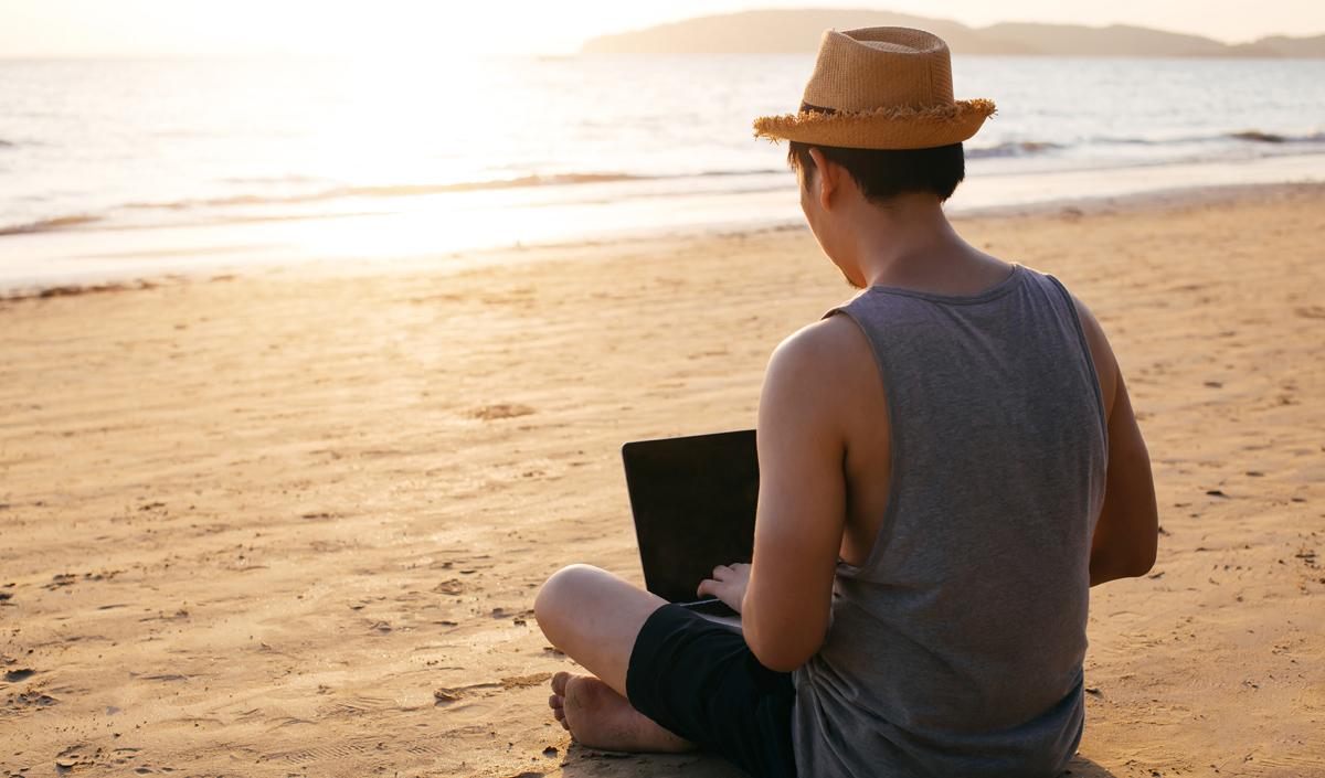 Anonymous freelancer using laptop near sea